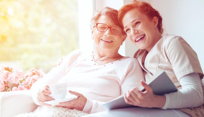 caregiver reading a book to senior woman