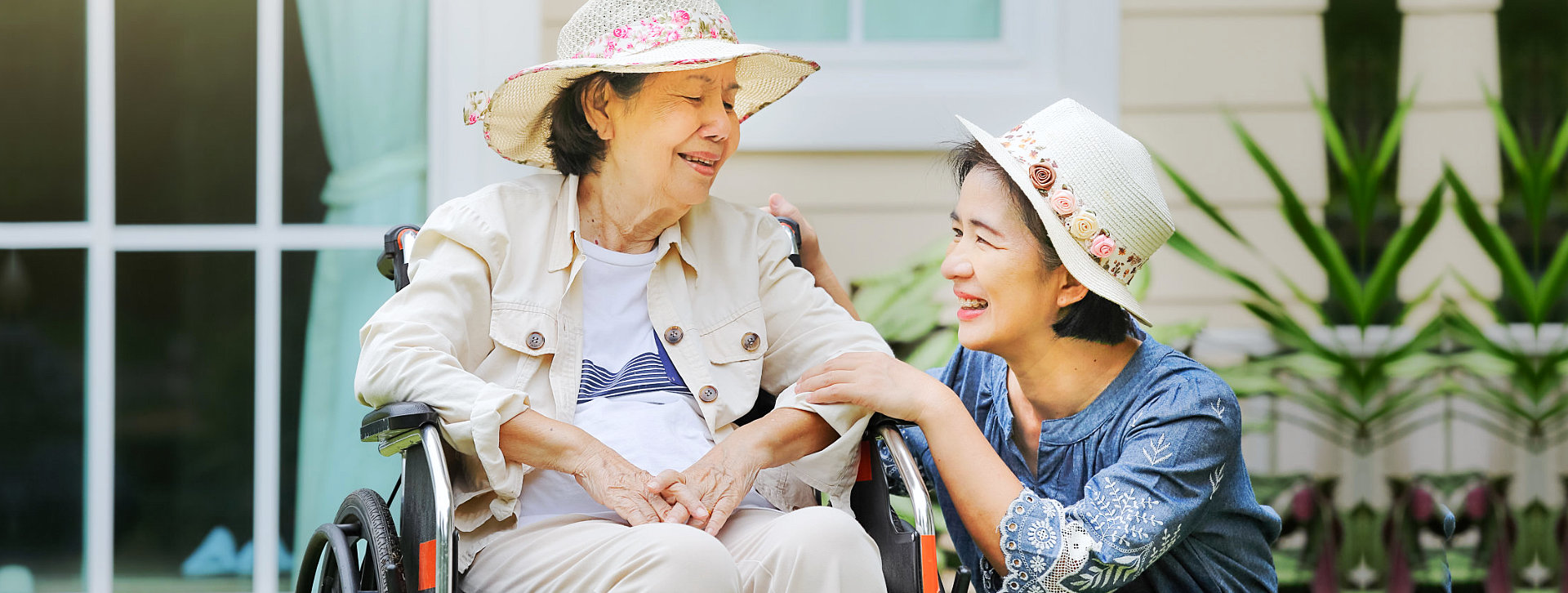 caregiver and senior woman in wheelchair smiling