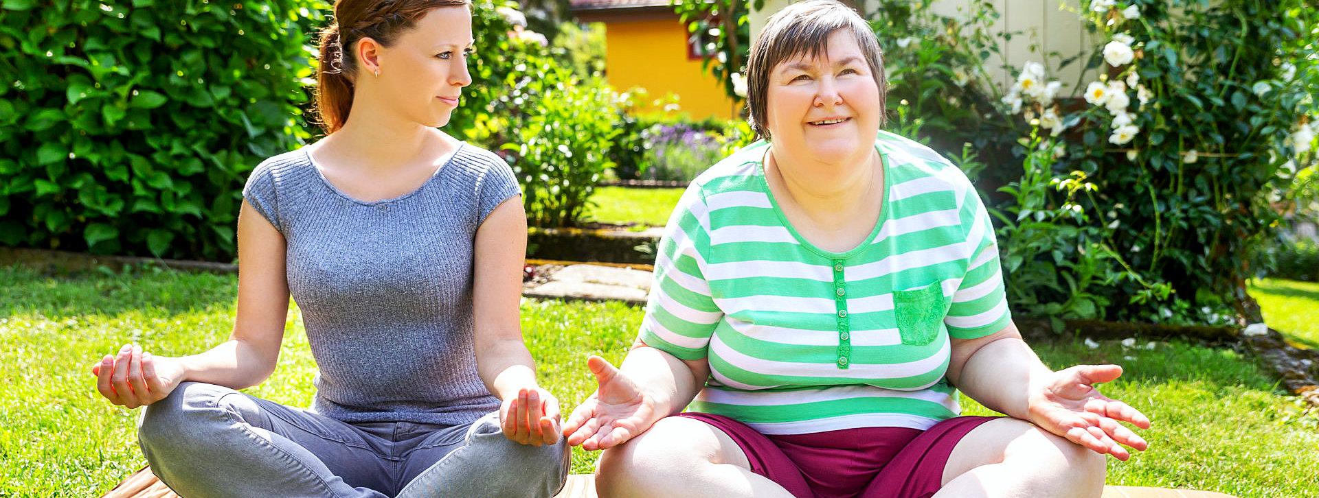 caregiver and senior woman doing meditating
