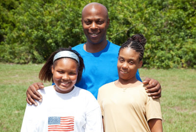 father along with her 2 daughters smiling