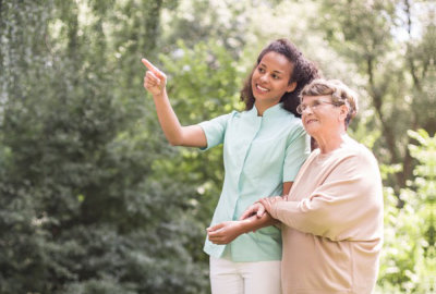 nurse walking along with a senior woman on the park